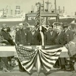 Joseph Vinson Roquemore (behind center of flag banner, to right of man with brass button tunic) at LA fire boat dedication; circa 1928